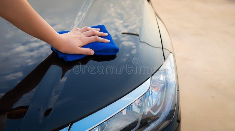 El primer de la mano de la mujer está limpiando su coche con el paño de la microfibra, el servicio del vehículo y el concepto de  fotos de archivo libres de regalías
