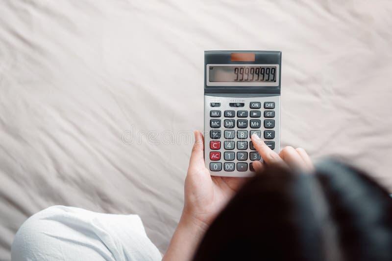 El primer de la mano de la mujer est? utilizando la calculadora para el ahorro o la demanda calculado en su dormitorio, negocio d fotos de archivo libres de regalías