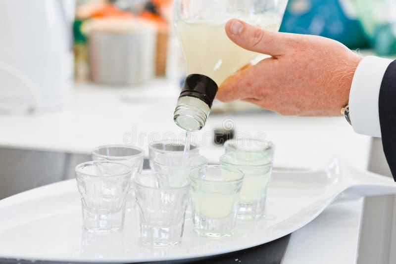 El primer de la mano de un camarero vierte una bebida en los vasos de medida, foco selectivo foto de archivo