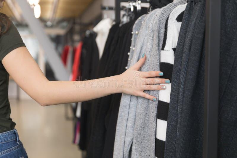 El primer de la mano de una muchacha se sostiene en la ropa colgante en la tienda foto de archivo libre de regalías