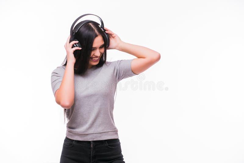 El primer de la muchacha caucásica morena feliz escucha baile la música con los auriculares imagen de archivo