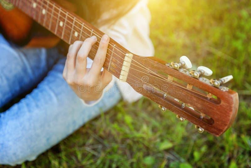 El primer de la mujer da tocar la guitarra ac?stica en fondo del parque o del jard?n Muchacha adolescente que aprende jugar la ca imagen de archivo