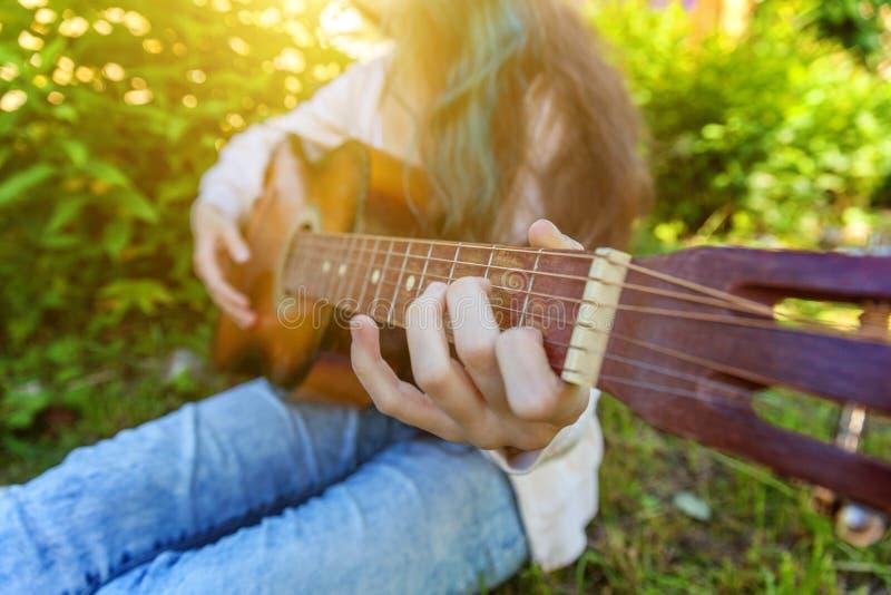 El primer de la mujer da tocar la guitarra ac?stica en fondo del parque o del jard?n Muchacha adolescente que aprende jugar la ca imagen de archivo libre de regalías