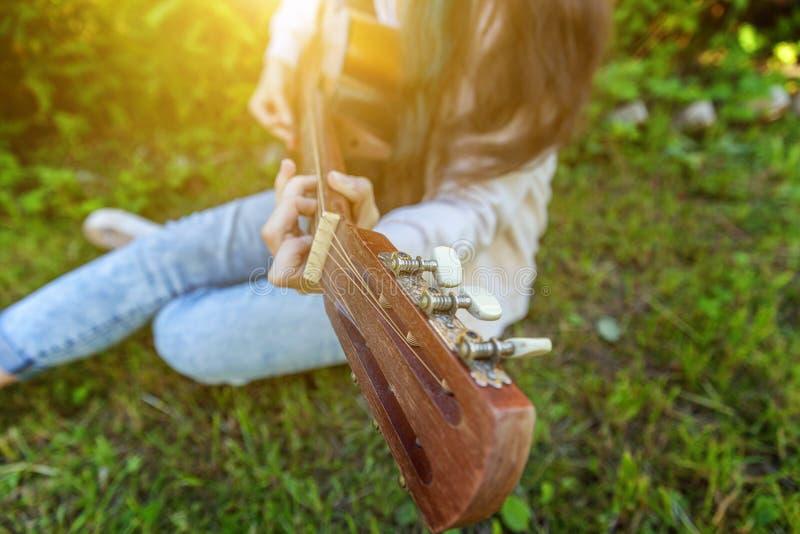 El primer de la mujer da tocar la guitarra ac?stica en fondo del parque o del jard?n Muchacha adolescente que aprende jugar la ca foto de archivo libre de regalías