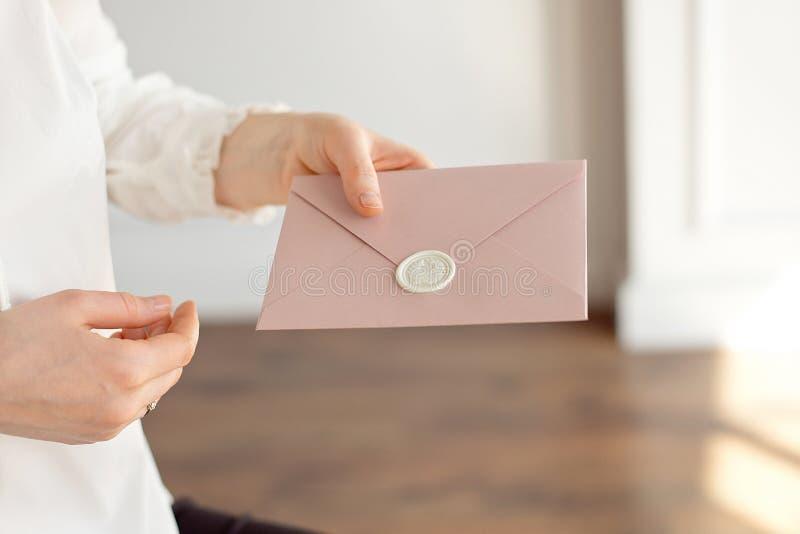 El primer de la mujer en la camisa blanca del estilo del negocio sostiene en su mano una tarjeta de la invitación, tarjeta, letra fotos de archivo libres de regalías