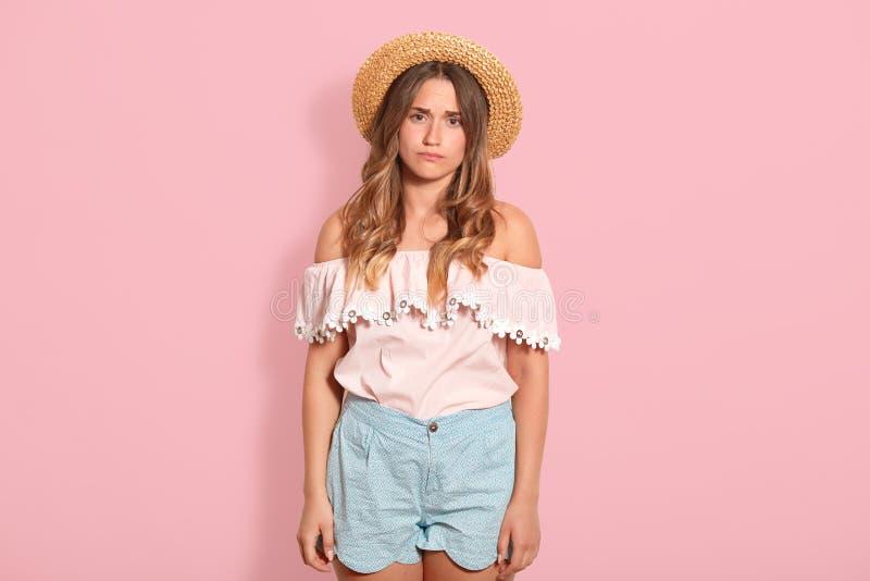 El primer de la mujer joven pensativa triste con el pelo ondulado y el sombrero de paja largos, ropa del verano que lleva, parece fotografía de archivo libre de regalías