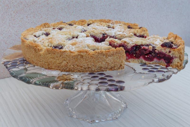 El primer de la torta de la cereza hizo en casa asperjado con el azúcar en polvo con un pedazo cortado, relleno visible imágenes de archivo libres de regalías