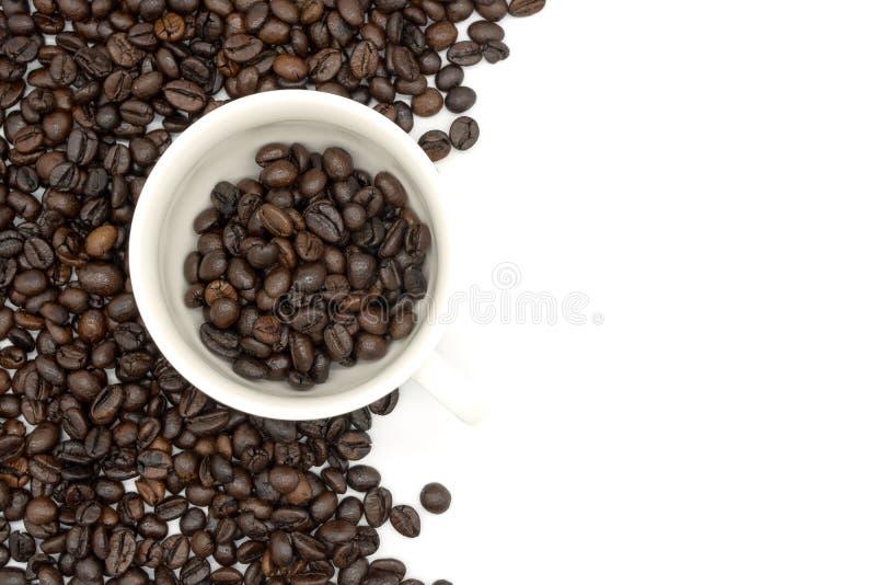 El primer de la visión superior de una taza de café llenó de los granos de café asados o de los granos de café asados aislados en imagen de archivo