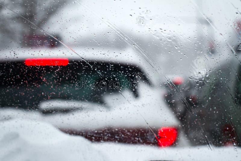 El primer de las gotas de lluvia llovizna en el parabrisas del coche imagen de archivo