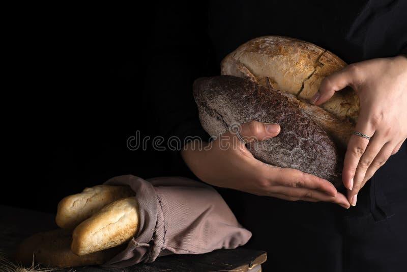 El primer de las manos de la mujer como corazón toma el pan fresco Foto oscura foto de archivo