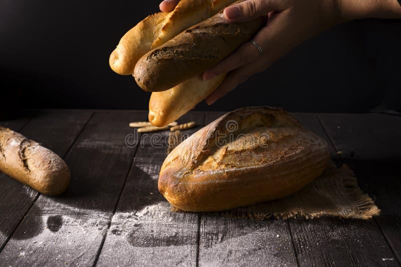 El primer de las manos de la mujer toma el pan fresco Foto oscura fotos de archivo libres de regalías