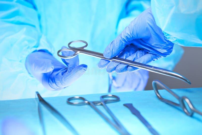 El primer de las manos de los cirujanos en el trabajo en teatro de operaciones entonó en azul imagen de archivo libre de regalías