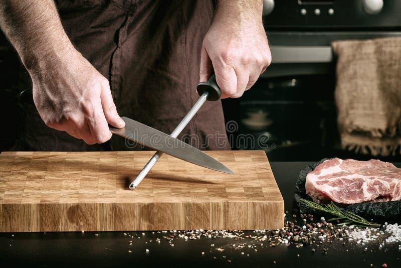 El primer de las manos masculinas del cocinero afila el cuchillo de un cocinero grande fotografía de archivo libre de regalías