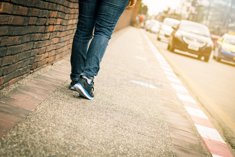 El primer de las piernas de la mujer joven camina en la acera foto de archivo libre de regalías