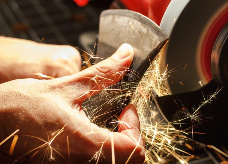 El primer de manos afila el hacha que afila la máquina imagen de archivo