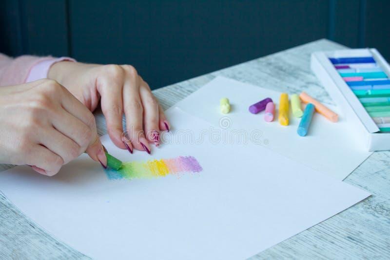 El primer de manos femeninas está dibujando con tizas multicoloras en una hoja blanca, una caja con los creyones fotos de archivo libres de regalías