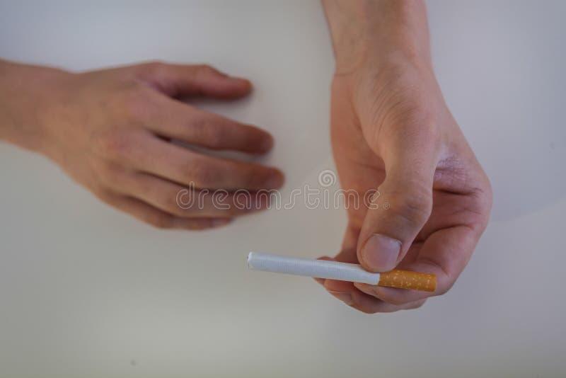 El primer de un cigarrillo se sostuvo en las manos foto de archivo