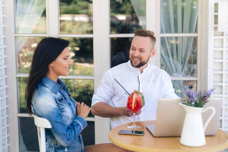 El primer de un hombre y una mujer se están sentando en una tabla, charlando alegre, discutiendo las últimas noticias, usando un  imagenes de archivo