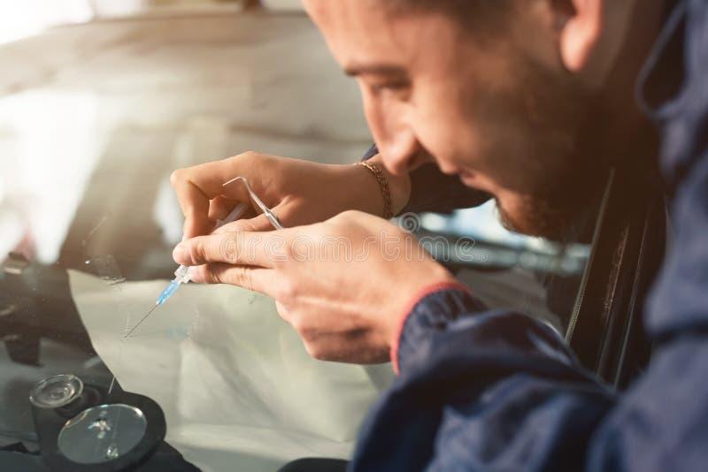 El primer de un reparador profesional del parabrisas llena una grieta en el vidrio de un polímero especial a través de una jering fotografía de archivo
