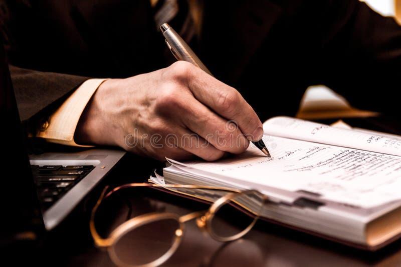 El primer de una mano del hombre de negocios escribe la información en diario foto de archivo