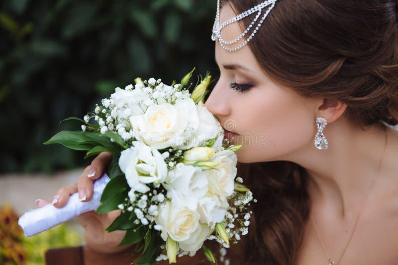 El primer de una muchacha hermosa joven en velo y lalactic, inhala la fragancia de sus flores en un ramo de la boda foto de archivo