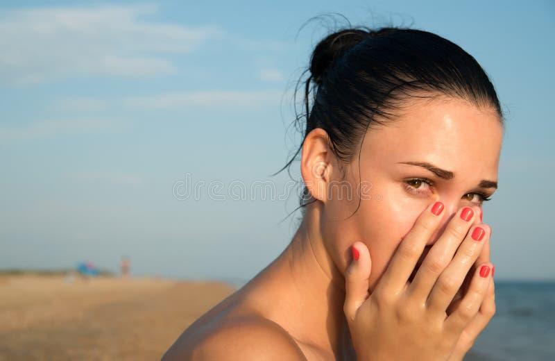 El primer de una mujer joven con el frotamiento rojo del ojo irritó sensi imagen de archivo