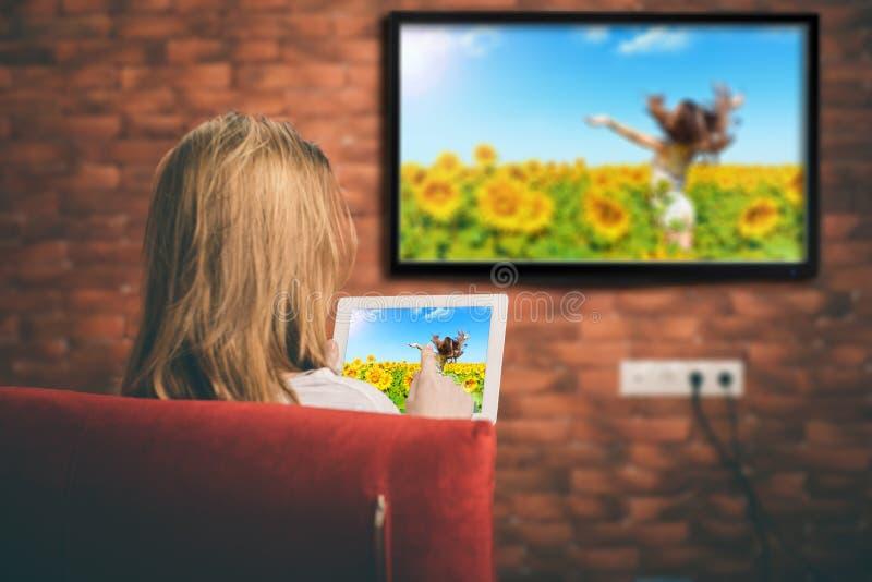 El primer de una tableta está conectado con una TV elegante foto de archivo