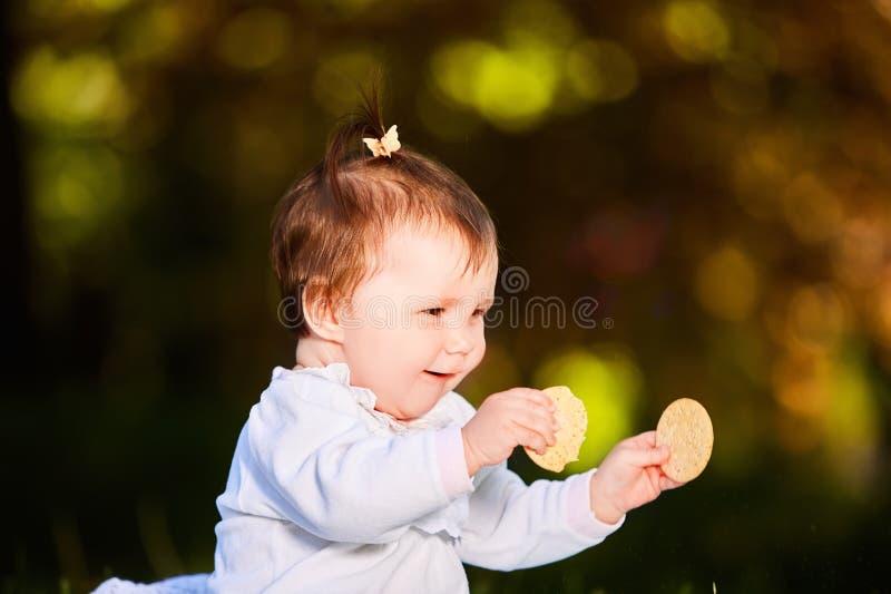 El primer del bebé lindo que se sienta en el parque y come el bocado en el día caliente fotos de archivo libres de regalías