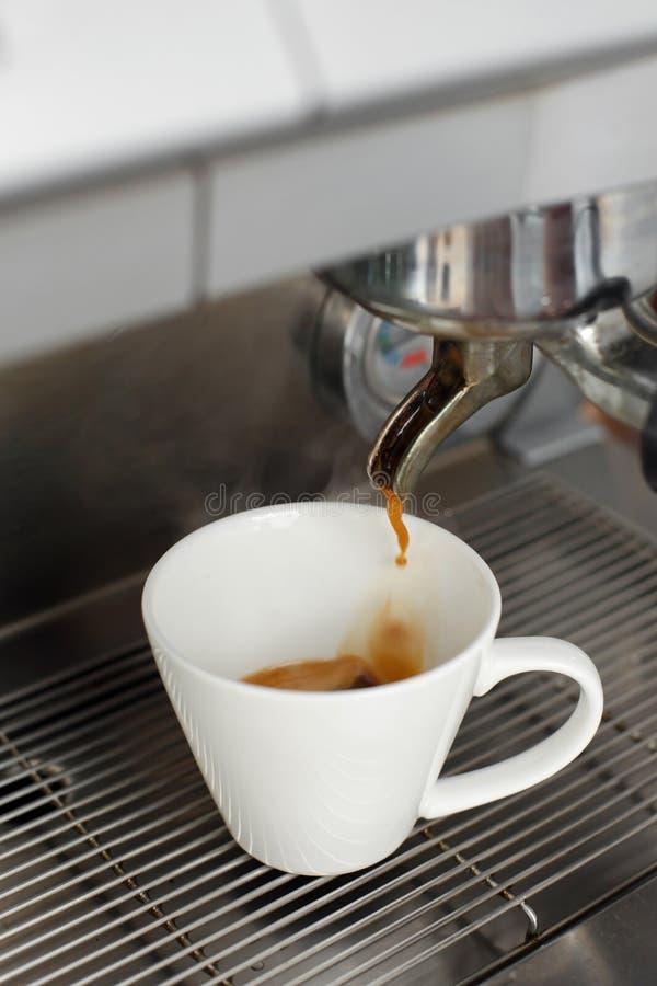 El primer del café recientemente preparado se vierte de una máquina del café en una taza blanca fotos de archivo libres de regalías