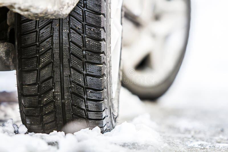 El primer del coche rueda adentro el neumático del invierno en el camino nevoso fotos de archivo