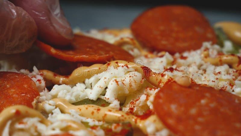 El primer del cocinero pone el salami en la pizza Cap?tulo El cocinero profesional pone la rebanada de salami en la pizza italian fotos de archivo