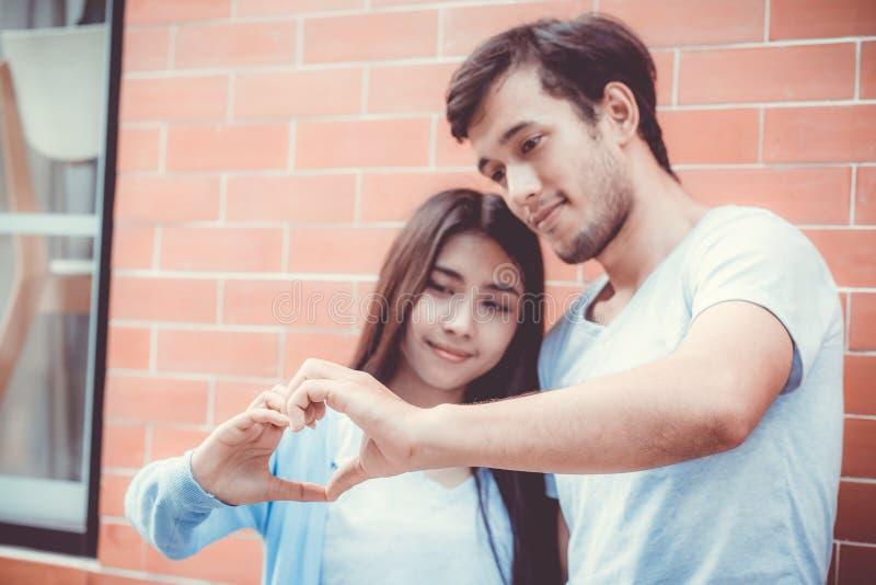 El primer del corazón de fabricación asiático del hombre joven y de la mujer forma con la mano imagen de archivo