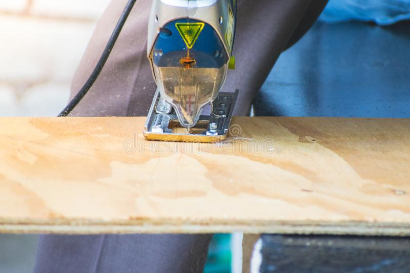 El primer del hombre del carpintero que usaba la circular vio para cortar la madera fotografía de archivo