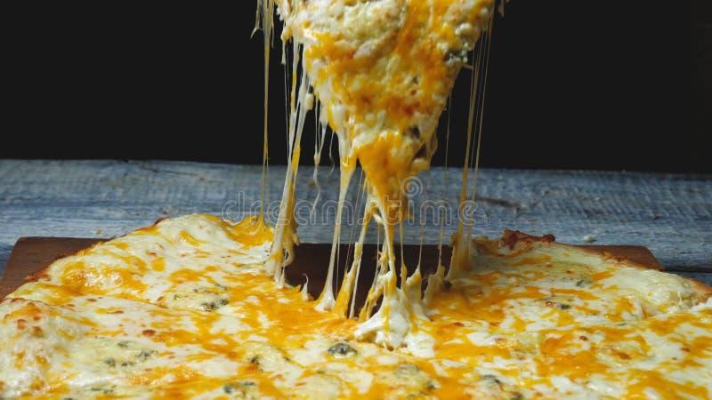 El primer del hombre toma la rebanada de pizza deliciosa con queso Cap?tulo El hombre toma el pedazo de pizza italiana y tira de  foto de archivo