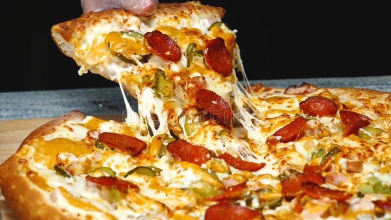 El primer del hombre toma la rebanada de pizza deliciosa con queso Cap?tulo El hombre toma el pedazo de pizza italiana y tira de  fotos de archivo libres de regalías