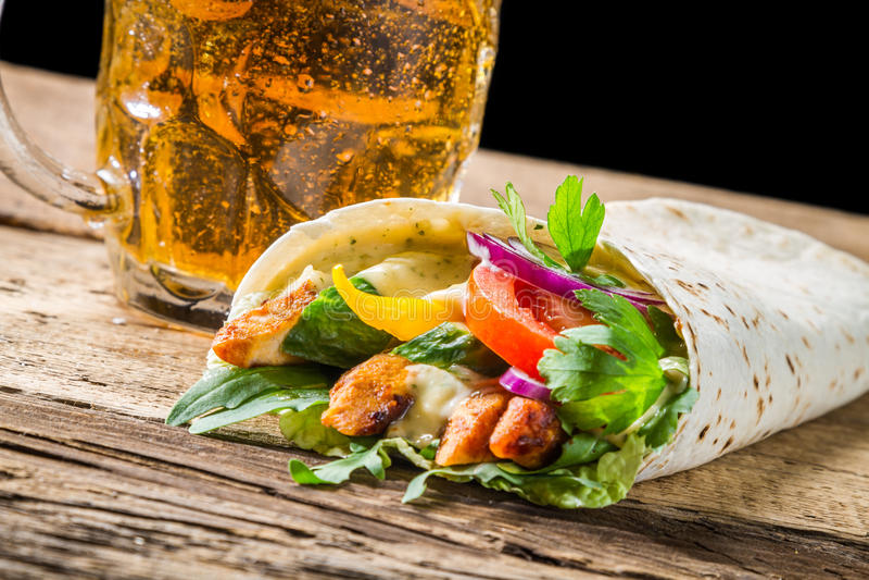 Primer del kebab servido con la cerveza fría fotografía de archivo