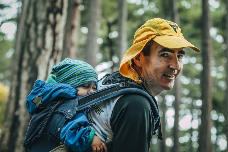 El primer del padre lleva a su niño en el suyo detrás en una mochila foto de archivo