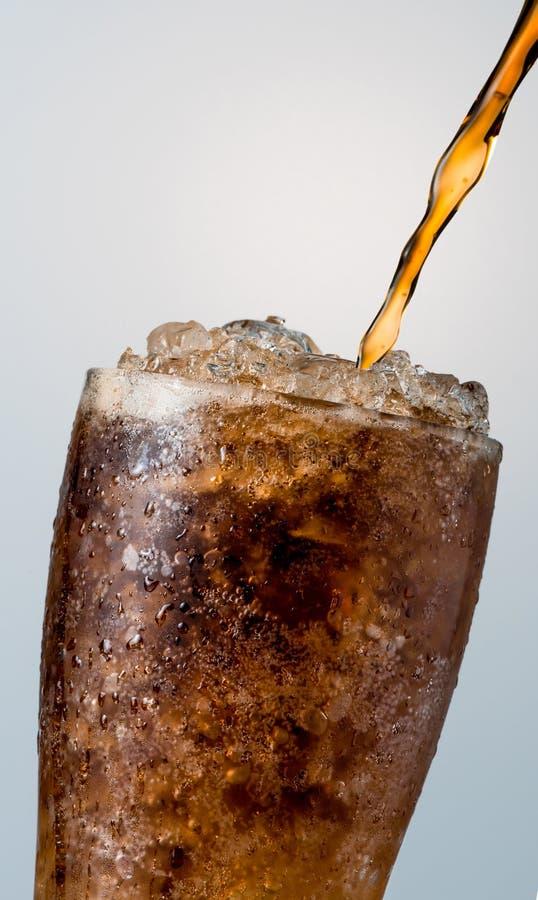 El primer del refresco que vierte al vidrio con los cubos de hielo machacados es imagenes de archivo