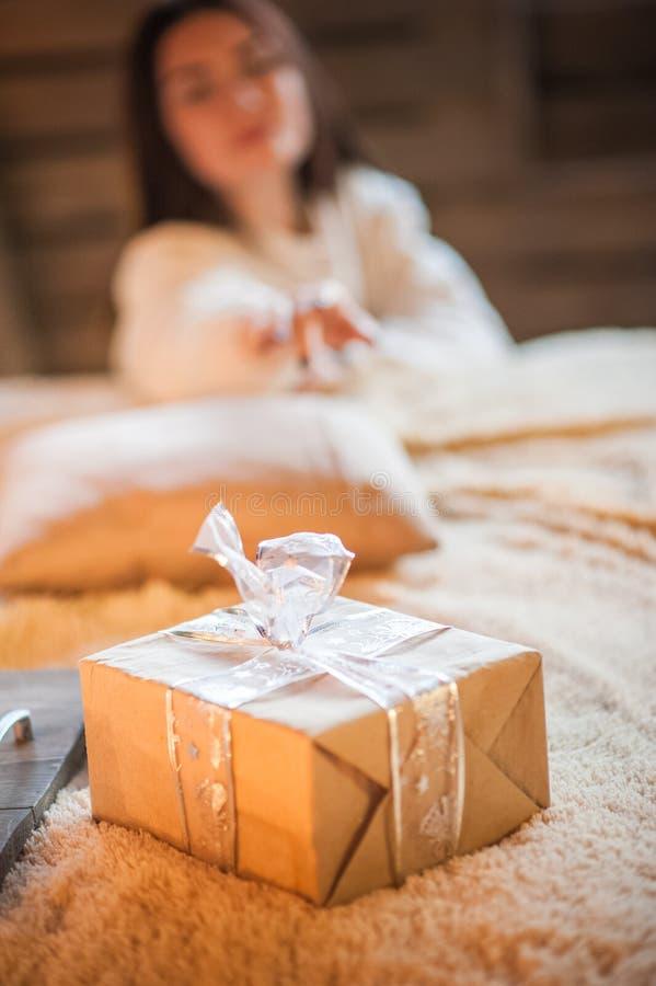 El primer del regalo del Año Nuevo, la muchacha alcanza hacia fuera para un regalo Dormitorio escandinavo del estilo interior baj imagen de archivo