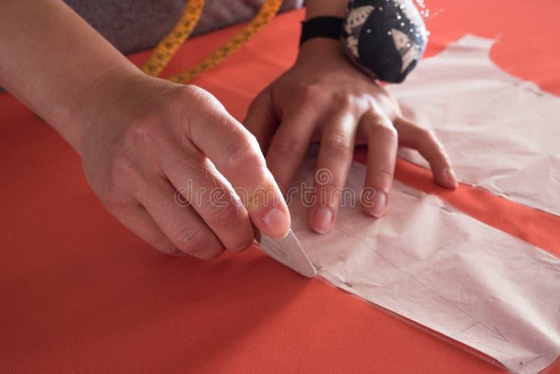 El primer del ` s del diseñador de moda de las mujeres da la marca con tiza en el paño en taller imagen de archivo