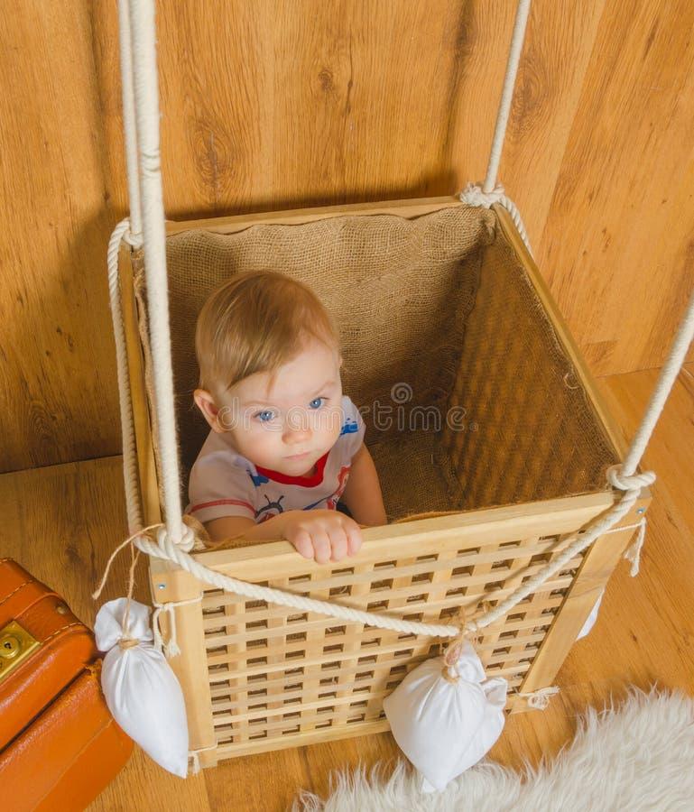 El primer, en la cesta del globo juega a un bebé del muchacho imagen de archivo libre de regalías