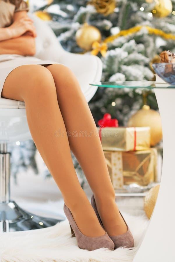 El primer en las piernas de la mujer joven acerca al árbol de navidad foto de archivo