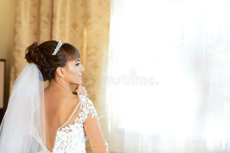 El primer entonó la foto de la novia hermosa que ataba encima de su vestido de boda mañana del día de boda de la novia fotografía de archivo