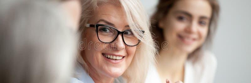 El primer envejeció al colega que escuchaba sonriente atractivo de la empresaria durante la reunión de informe fotos de archivo