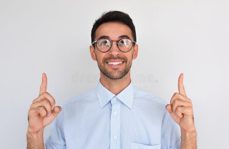 El primer horizontal tirado de puntos masculinos caucásicos satisfechos felices hacia arriba con ambos dedos índices, nota algo a fotos de archivo libres de regalías
