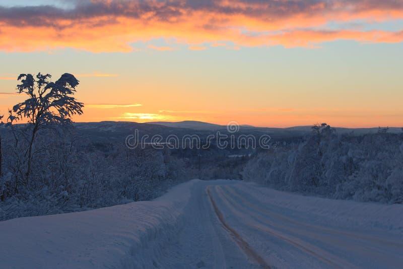 El primer sol irradia en el camino en el bosque septentrional nevado del invierno después de la noche polar fotos de archivo libres de regalías