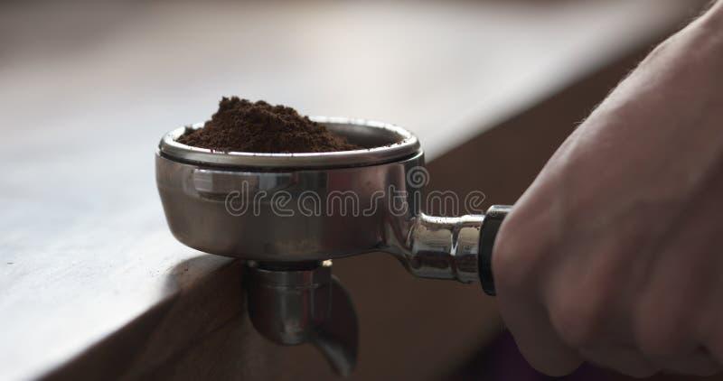 El primer tiró de apisonar el café molido fresco para preparar el café express imagen de archivo libre de regalías