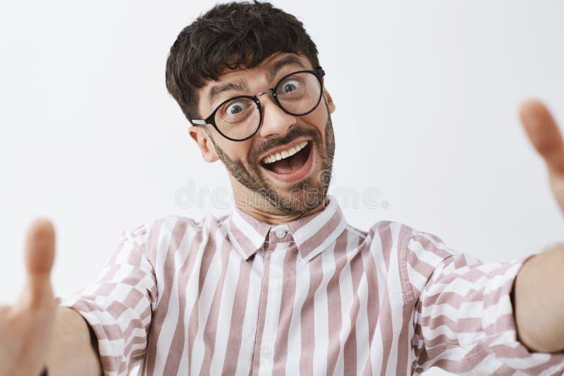 El primer tiró de inconformista masculino moderno apuesto emotivo y feliz divertido en vidrios y la tracción de la camisa rayada  imágenes de archivo libres de regalías
