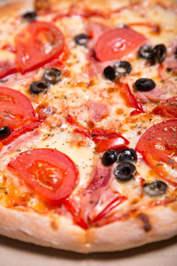 El primer tiró de la pizza italiana deliciosa con el jamón, tomates y imagen de archivo