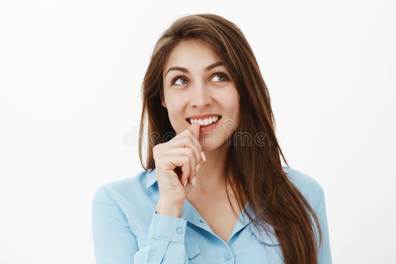 El primer tiró de morenita creativa hermosa en blusa azul, pulgar penetrante y mirar soñador la esquina superior derecha imagen de archivo libre de regalías